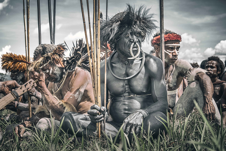 Portrait of a Dani leader with his warriors (Papua, Indonesia).