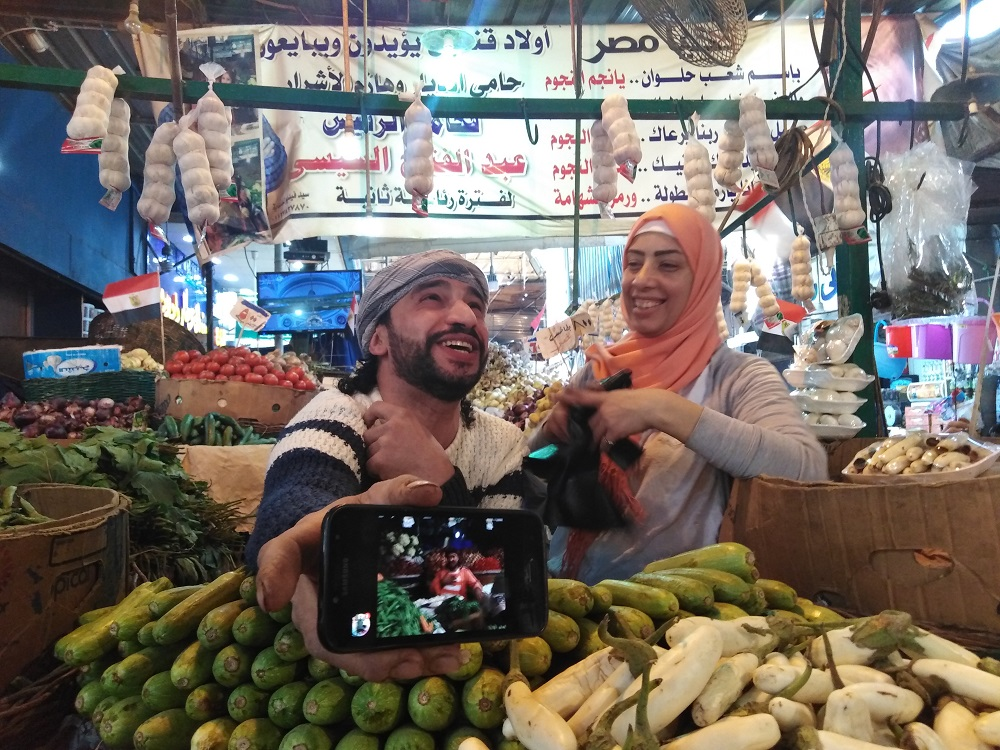 A vegetable vendor proudly showing his youtube channel that he daily post to his shop updates. Nourhan Ebrahim
